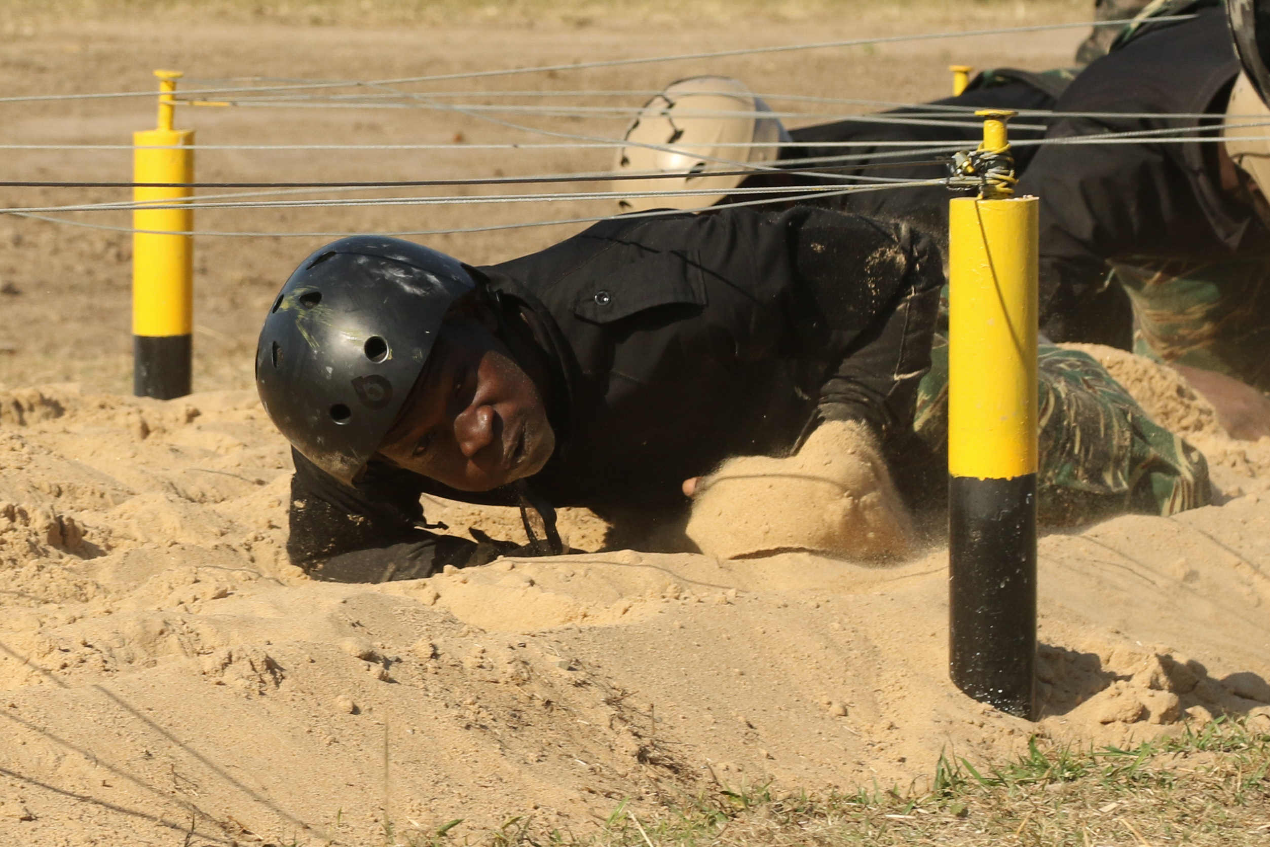 A Guyanese comando crawls beneath wires during a Fuerzas Comando obstacle course July 24, 2017, in Vista Alegre, Paraguay. This competition increases training knowledge and furthers interoperability between countries in the Western Hemisphere. (U.S. Army photo by Sgt. Joanna Bradshaw/Released)